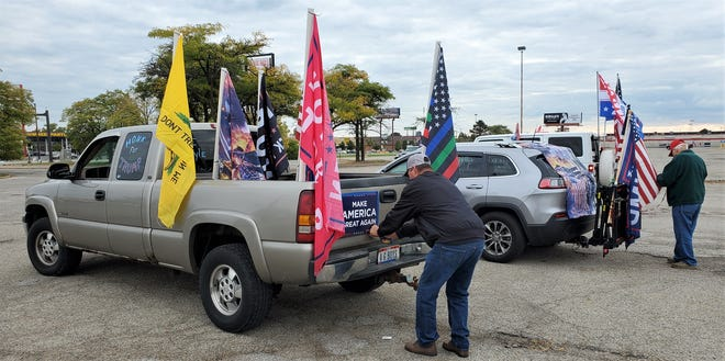 "Scott Agee attaches a ""Make America Great Again"" sign to the tailgate of his flag-festooned pickup truck prior to joining other supporters of President Donald Trump in driving a lap around I-270 on Saturday. [Randy Ludlow/Dispatch]"