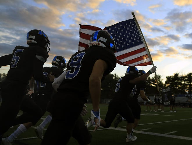 Harrison Kline (6) of Worthington Kilbourne carries an American flag onto the field before the Wolves' game Friday against Westerville North. [Kyle Robertson/Dispatch]