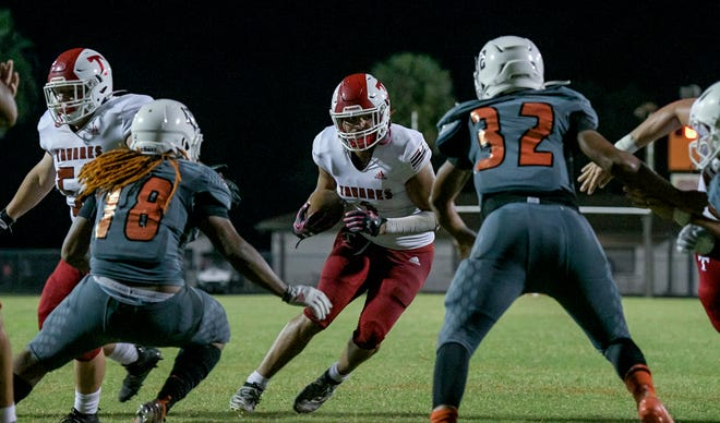 Tavares' Angelo McDowell (1) runs up the middle in Friday's game against Leesburg at H.O. Dabney Stadium in Leesburg. [PAUL RYAN / CORRESPONDENT]