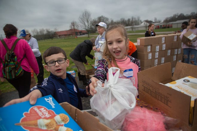 Kyle Pewitt, 7, and  Julia Roper, 9, help distribute food at a mobile food center hosted by the The Well Outreach at Spring Hill High School on Saturday, March 9, 2019.