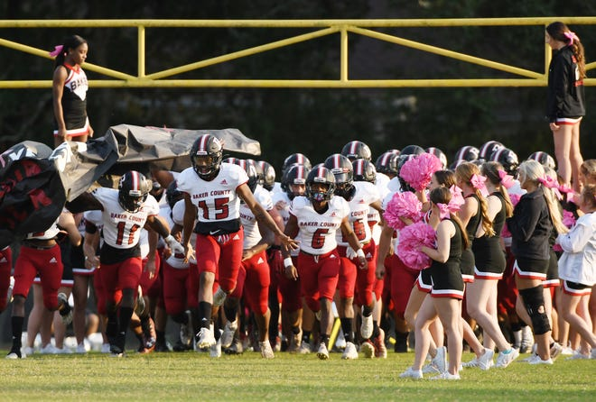 Baker County's players charge onto the field before an Oct. 2 game against Westside.
