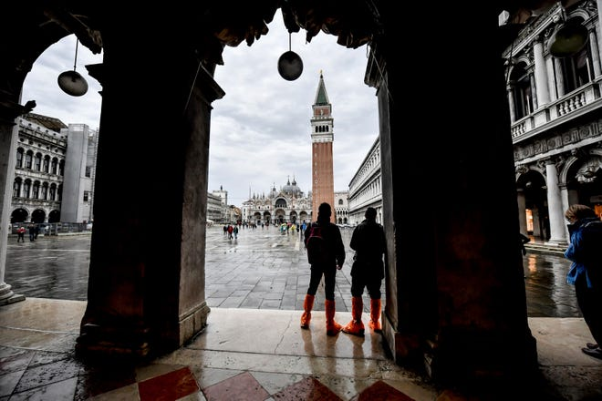 People wear waders as they observe St. Mark's Square during an expected high water, in Venice, northern Italy, on Saturday. Controversial and long-delayed underwater barriers passed their first emergency with flying colors on Saturday, protecting the Italian lagoon city of Venice from a tide that peaked at 51 inches, a level that would normally inundate about half of the city.