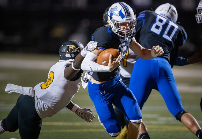 Lakeland Christian quarterback Elijah Hunter (15) eludes Fort Meade Jonathan Berrien (8) as he scrambles for yardage during the first half at LCS in Lakeland earlier this month.
