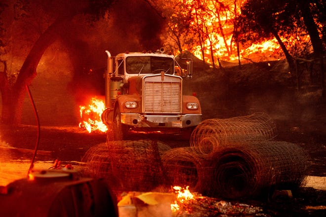 Flames from the Glass Fire burn a truck in a Calistoga, Calif., vineyard Thursday.