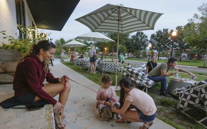 Jessica Carpenter looks on as Jamie and Jordan Wiedersheim play with her dachshunds Sophie and Oakley outside the Joinery on Friday night. Downtown Lakeland bars and restaurants opened to full capacity for Phase 3.