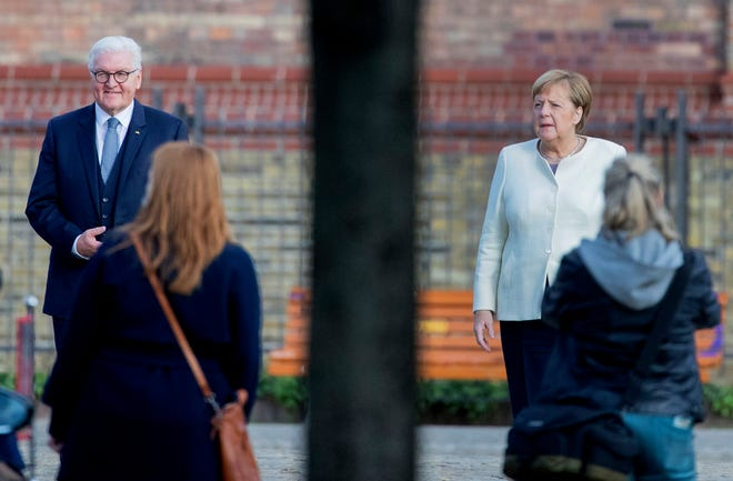 Federal President Frank-Walter Steinmeier and Federal Chancellor Angela Merkel stand in front of the church of St. Peter and Paul before an ecumenical service, Berlin, Germany, on Saturday. Potsdam, as the capital of Brandenburg, will host this year's central celebrations of the Day of German Unity.