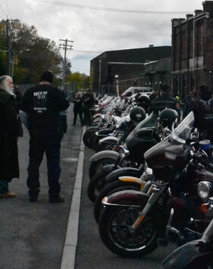 """People congregate near some of the 65 motorcycles that were part of the """"Back the Blue"""" rally Saturday that ended with a rally on Water Street in Utica."""