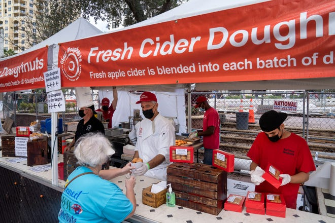 Fresh Cider Doughnuts serving customers at their stand at the West Palm Beach GreenMarket in West Palm Beach in 2020.