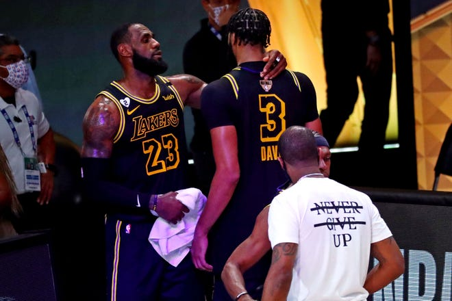 Los Angeles Lakers forward LeBron James (23) celebrates with forward Anthony Davis (3) after defeating the Miami Heat in Game 2 of the 2020 NBA Finals at AdventHealth Arena. [Kim Klement/USA TODAY Sports]