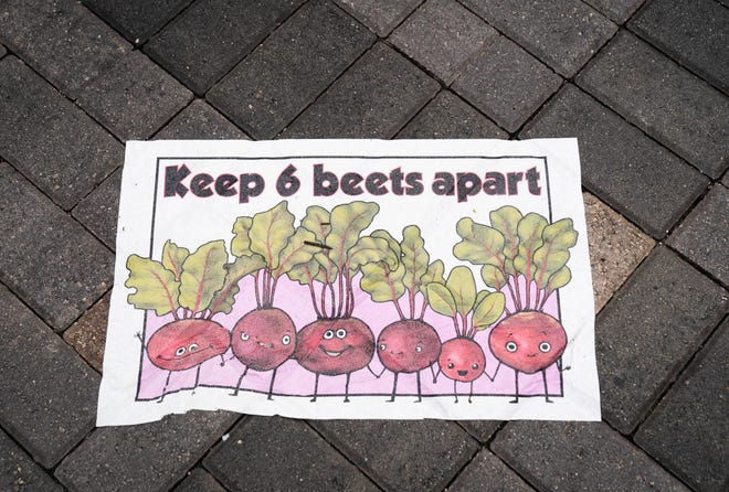 Signs on the ground reminds visitors to socially distance themselves while attending the West Palm Beach GreenMarket opening in West Palm Beach, Florida on October 3, 2020.