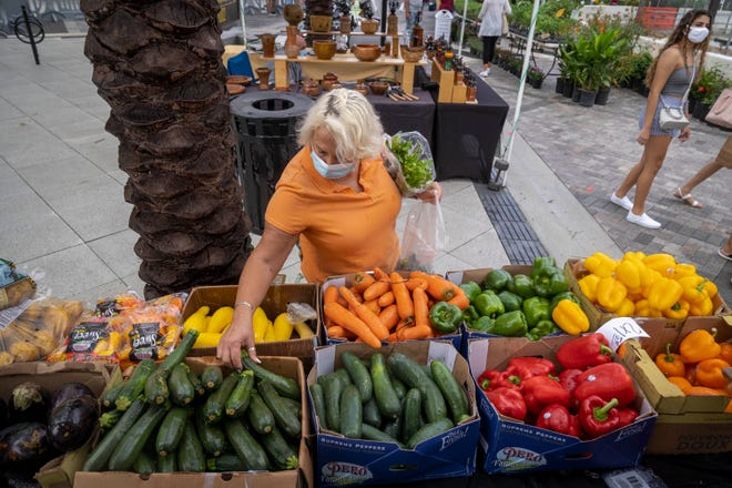Raffaella Caesar looks at fruits and vegetables from Continental Produce at the West Palm Beach GreenMarket in West Palm Beach on October 3, 2020.