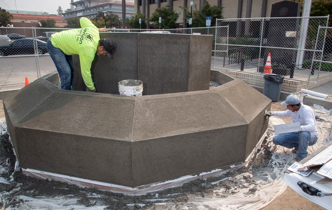 Jose Ruiz Lopez, left, and Heriberto Estudillo Rodriguez with Stockton-based Kenyon Plastering Inc. apply plaster over the brick base of the new San Joaquin County Peace Officer Memorial being built in front of the Stockton Police Department. The memorial will be surrounded by a small plaza of donor-purchased bricks.