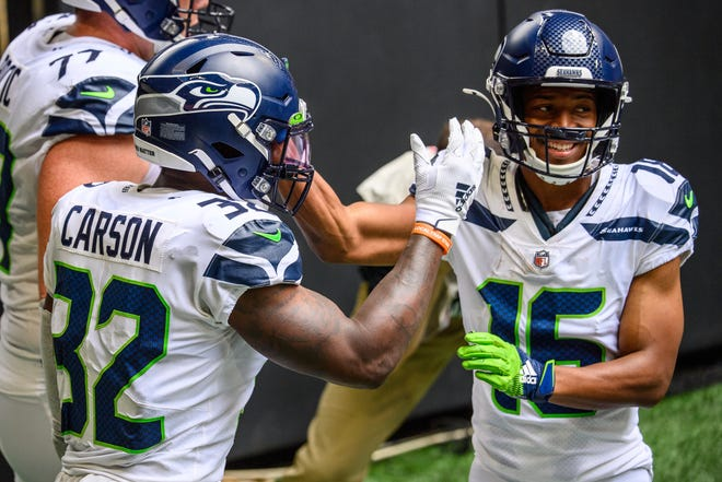 Running back Chris Carson (32), wide receiver Tyler Lockett and the Seattle Seahawks take their 3-0 record into Sunday's game against the Miami Dolphins.
