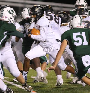 Central Catholic's defense, including Owen Murphy (51), tries to surround St. Thomas Aquinas' Asian Burt during the two rivals' Week 6 game.