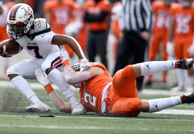 Massillon's Caiden Woullard brings down McKinley quarterback Elijah Wesley during the Tigers' win last Saturday.