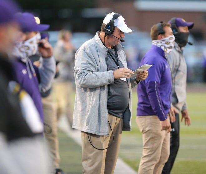 Jackson coach Tim Budd checks his play sheet during his team's game against Hoover last Friday night.