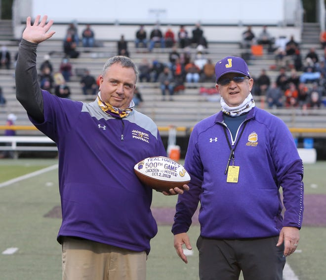 Teal Harvey (left) is presented a football by Jackson Athletic Director Dan Michel in honor Harvey's 500th football game prior to Jackson playing Hoover on Friday, Oct. 2, 2020. Harvey is a long time statistician for the Polar Bears.