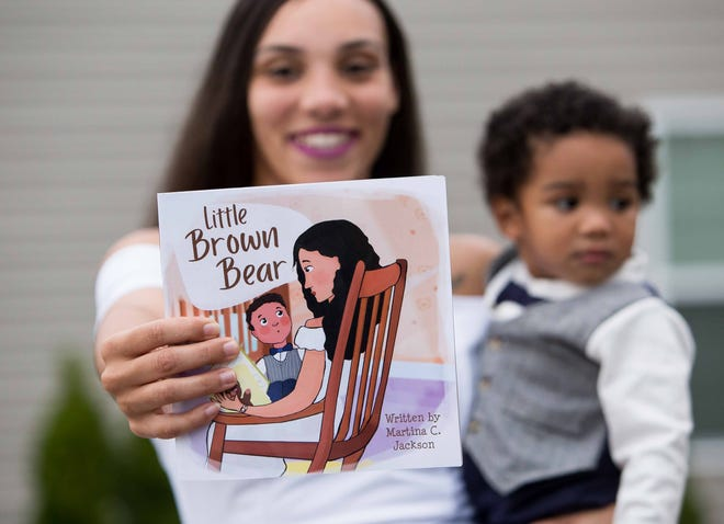 "Author Martina Jackson holds the cover of her new children's book ""Little Brown Bear,"" starring her and her 15-month-old son, Kyrie."