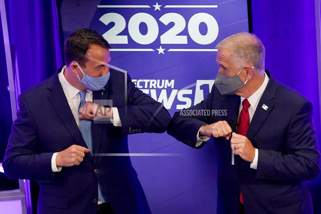 Democratic challenger Cal Cunningham, left, and U.S. Sen. Thom Tillis, R-N.C. greet each other after a televised debate Thursday in Raleigh. (AP Photo/Gerry Broome, Pool)