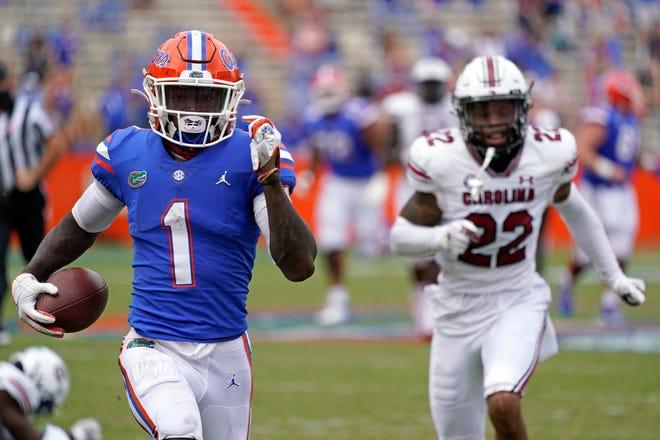 Florida wide receiver Kadarius Toney gets past South Carolina defensive back John Dixon (22) for a 57-yard touchdown run during the second half Saturday.