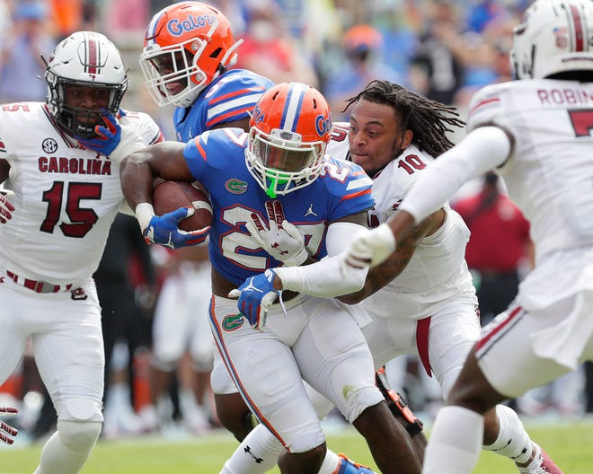 Florida running back Dameon Pierce (27) is tackled by helmet-less South Carolina defensive back RL Roderick as he runs near the end zone Saturday at Ben Hill Griffin Stadium. Pierce would score from the two later in the drive.