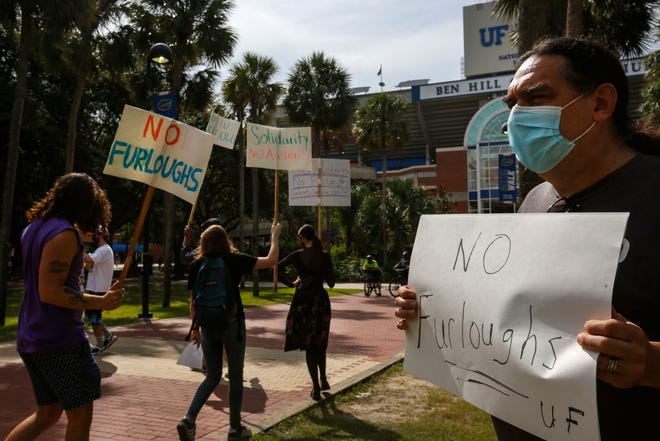 Paul Ortiz, a professor of history at the University of Florida and president of UF's faculty union, pickets with other protestors against furlough outside of Ben Hill Griffin Stadium in Gainesville on Oct. 3.