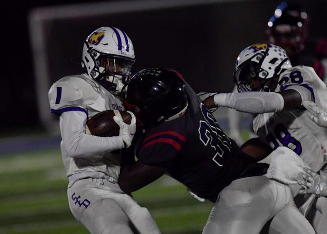 Hartley's Marcelis Parker stops DeSales' Jordan Johnson on a punt return during the teams' game Oct. 2 at Hartley. DeSales' Quintell Quinn (28) also was in on the play. DeSales won 16-14.
