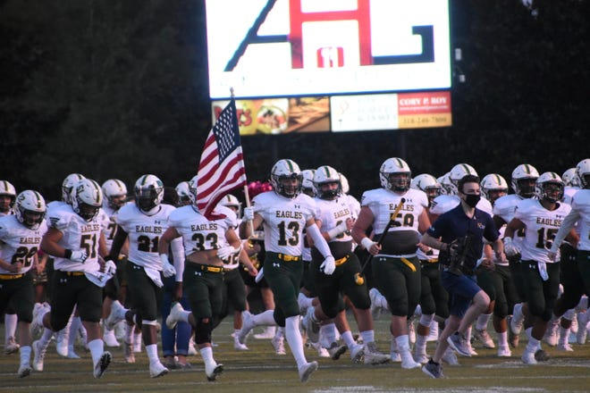 Holy Savior Menard players run onto the field before its game against Homer Friday, Oct. 2, 2020.