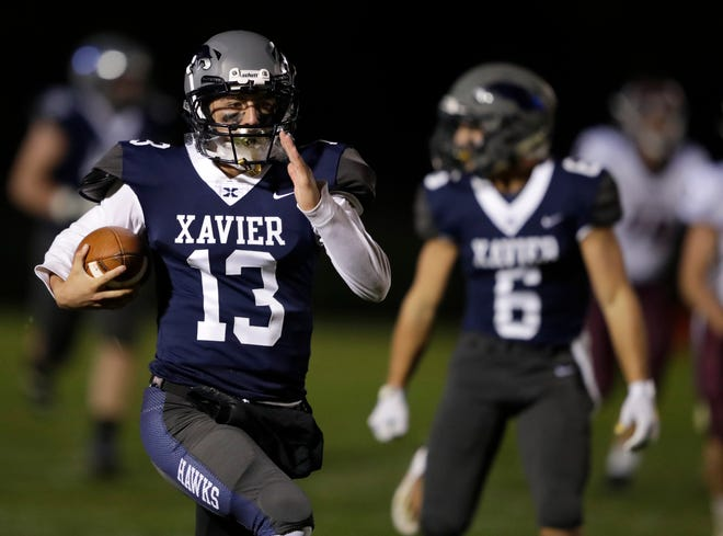 Xavier's Ray Zuleger (13) breaks away for a long touchdown run against Fox Valley Lutheran to give his team a 7-6 lead during their football game Oct. 2 at Xavier High School in Appleton. Xavier won 54-18.