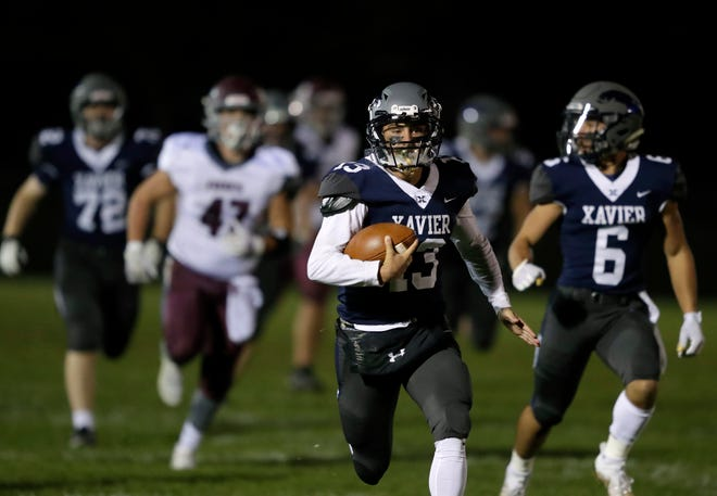 Xavier's Ray Zuleger (13) breaks away for a long touchdown run against Fox Valley Lutheran during Friday's Apple Bowl game at Xavier.
