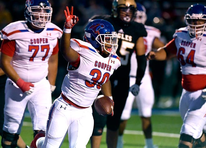 Cooper running back Jeremiah Riley raises a hand in celebration after scoring a touchdown against Abilene High during last year's game at Shotwell Stadium. Cooper won the 60th meeting 30-20.