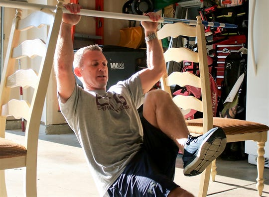 South Kitsap High School physical education teacher Chad Nass demonstrates an exercise using two chairs and a pole from the garage in his house in Port Orchard on Oct. 2.