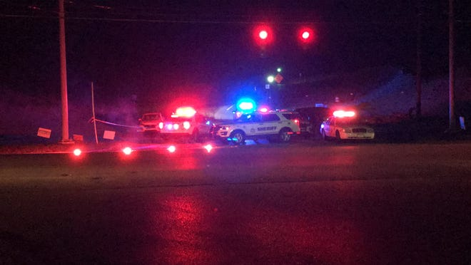 Police took a suspect into custody from a white car at left at Grand National Boulevard and Ky. 338 after a woman was fatally shot and 3-year-old and 30-year-old man were shot and injured in Boone County.