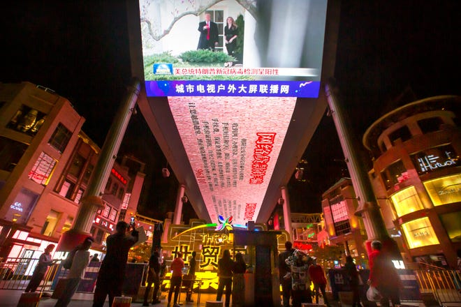 People watch a large screen showing President Donald Trump and First Lady Melania Trump during a news report from Chinese state television about Trump testing positive for the coronavirus in Beijing, Friday, Oct. 2, 2020.