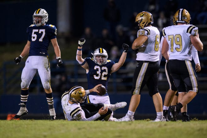 Castle's Sam Rolley (57) and Castle's Brice Maslanka (32) celebrate after sacking Jasper Quarterback Blake Mann (5) in the third quarter at John Lidy Field in Newburgh, Ind., Friday, Oct. 2, 2020. The Knights defeated the Wildcats, 14-10.