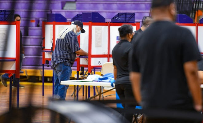 Voter Mark Muna makes his selections on his absentee ballot during Guam Election Commission satellite location voting at the George Washington High School in Mangilao on Saturday, Oct. 3, 2020.
