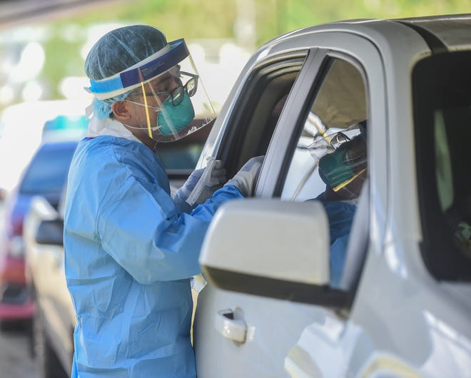 Nurses and volunteers from the Guam Department of Public Health and Social Services, Guam Department of Education, Guam Community College, and University of Guam conduct free COVID-19 drive-thru tests at the Umatac Mayor's Office in this Oct. 3 file photo.