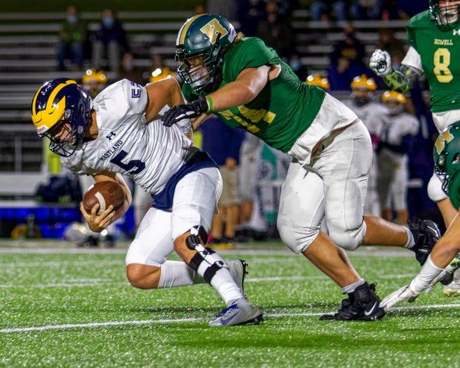 Howell's Ethan Lasssiter hauls down Hartland quarterback Holden D'Arcy on Friday, Oct. 2, 2020.