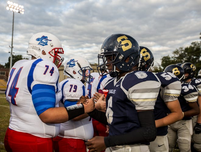 Players lined up for handshakes after Jackson County head coach John Hallock delivered an impassioned speech about race and acceptance before the game between the Generals and Golden Eagles on Oct. 2, 2020.
