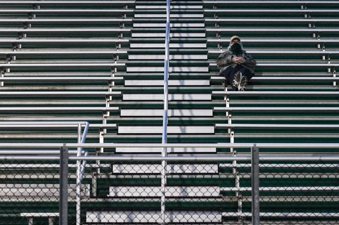 A Williamston football fan practices social distancing during the Hornet's game against the Haslett Vikings, Friday, Oct. 2, 2020.  The Hornets won 17-13 at home.