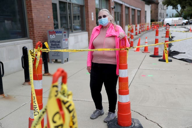 Deborah Epps stands outside the Washington Park Library on 2121 N. Sherman Blvd. in Milwaukee on Saturday. Earlier in the week Epps had trouble submitting her absentee ballot to the drop box  at the library due to construction in the parking lot that was blocking the sidewalk.