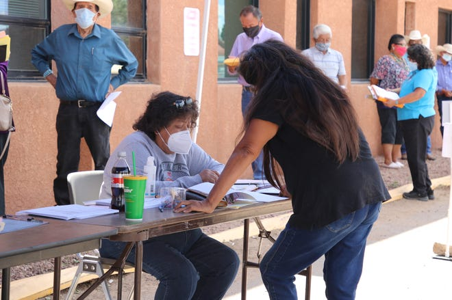 An employee with the Navajo Election Administration helps an individual file candidacy paperwork on Aug. 10, 2020 in Window Rock, Arizona for the tribe's general election.