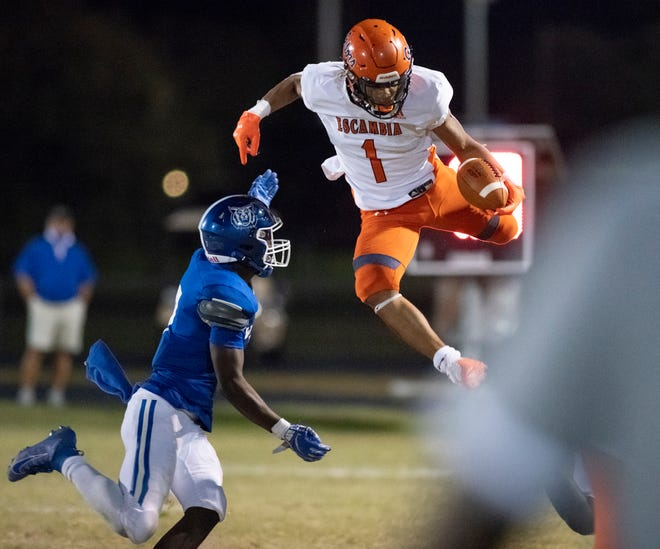 Jojo Blackmon (1) goes airborne while carrying the ball during the Escambia vs Washington football game at Booker T. Washington High School in Pensacola on Friday, Oct. 2, 2020.