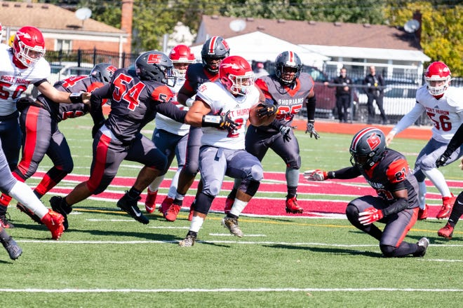 Lake Shore's Aiden Houth (54) reaches to stop Port Huron's Caleb Collier as he runs the ball during their game Saturday, Oct. 3, 2020, at Lake Shore High School.