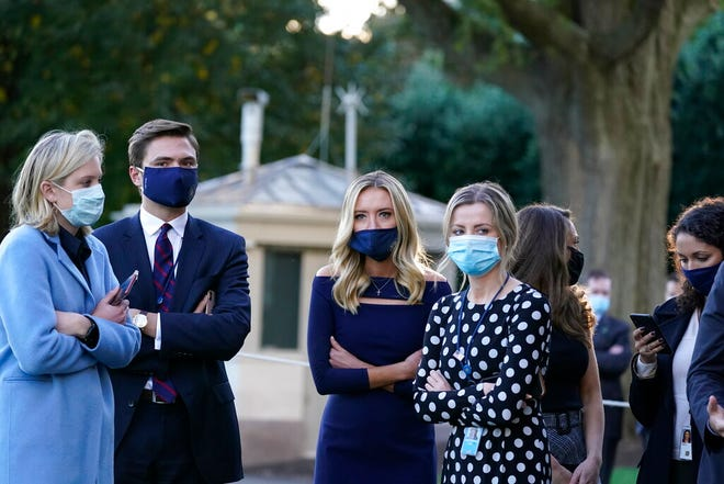 White House press secretary Kayleigh McEnany, third from left, waits with others as President Donald Trump prepares to leave the White House to go to Walter Reed National Military Medical Center after he tested positive for COVID-19, Friday, Oct. 2, 2020, in Washington. (AP Photo/Alex Brandon)