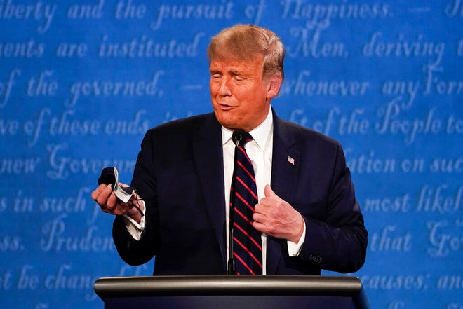 President Donald Trump holds out his face mask during the first presidential debate at Case Western University and Cleveland Clinic, in Cleveland, Ohio, Sept. 29, 2020. (AP Photo/Julio Cortez)
