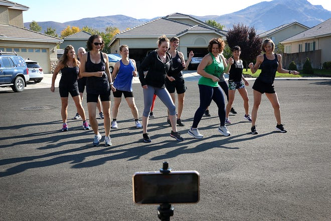 The ladies of Breast Cancer 2 Bikini record a dance performance for a friend with cancer after a training session at their coach Gina Benedict's home gym in Reno on Oct. 3, 2020.