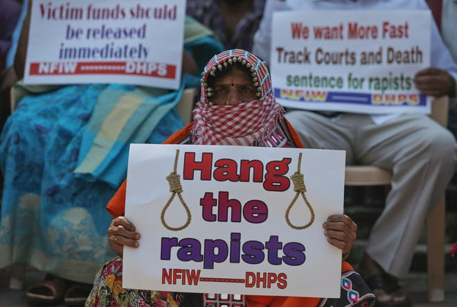 "An activist holds a placard reading ""Hang the rapists"" during a protest against the gang rape and killing of a Dalit (lowest caste) woman in India's northern state of Uttar Pradesh, in Hyderabad, India, Friday, Oct. 2, 2020."