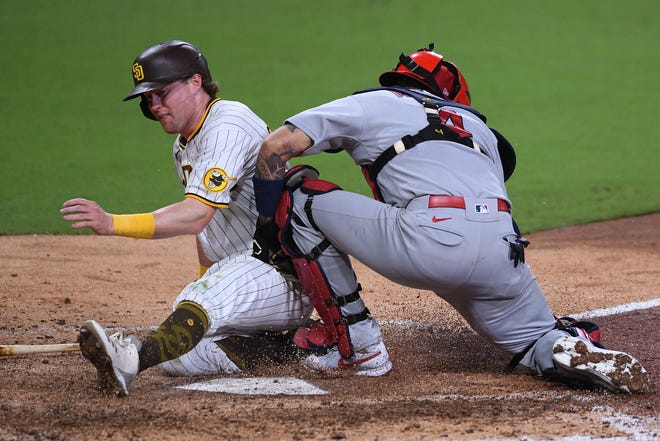 Padres-Cardinals, Game 3: Jake Cronenworth scores as St. Louis Cardinals catcher Yadier Molina (4) cannot handle the throw during the seventh inning.