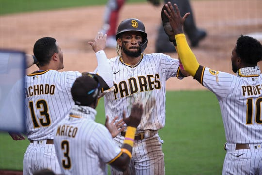 Padres-Cardinals, Game 3: Fernando Tatis Jr. celebrates with teammates after scoring a run in the fifth inning.